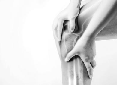Image of person holding their knee in pain - Click here to read about our orthopedic specialties