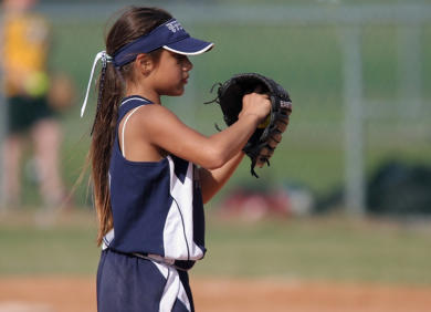 Photo of young girl playing softball - Click here to open a sports physical form (opens in a new tab or window)