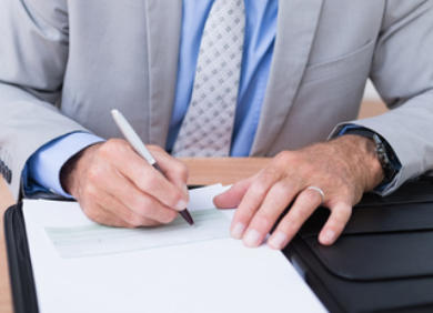 Photo of man signing papers - Click here to read about statements and notices